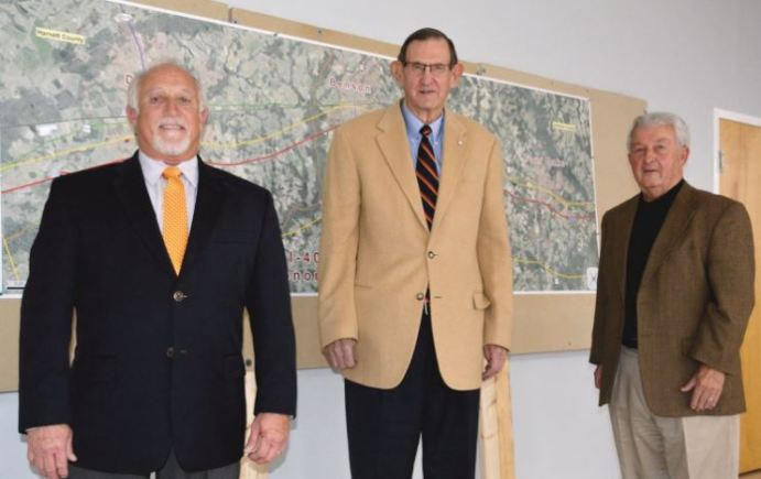 From left, Dunn Mayor William Elmore, Besnon Mayor Jerry Medlin and Four Oaks Mayor Linwood Parker stand in front of a map of the I-95/I-40 crossroads they hope to turn into an economic boom for the area. Dunn Daily Record Photo