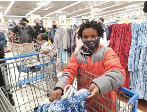 Myadrian Myers, 9, shows off a two-layer coat in his shopping cart during Shop with a Cop Tuesday morning. In the background, 8-year-old Mykayla McDonald waits to do more shopping as Gospel Tabernacle Pastor Randy Hill, from left, Erwin police Chief Jonathan Johnson, Dunn police Chief Clark White and Dunn Lt. Cary Jackson look on. Dunn Daily Record Photo