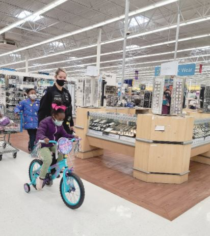 Four-year-old Kaya Halsey rides her new bicycle during Shop with a Cop as Erwin police Officer Destiny Johnson stays by her side. Nine-year-old Skylar Beck pulls a shopping cart with more goodies behind. Dunn Daily Record Photo