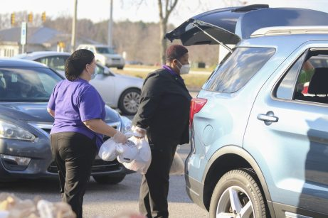 JCPS School Nutrition staff members Jennie Woodard (left) and Sherita Cox (right) load Holiday Meal Kits into vehicles at Smithfield-Selma High on Thursday, Dec. 17.