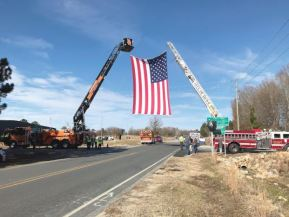 An American flag, held up by two ladder trucks, is draped over the road where Sarah Lewis' body will pass through. Photo by Thomas Honeycutt