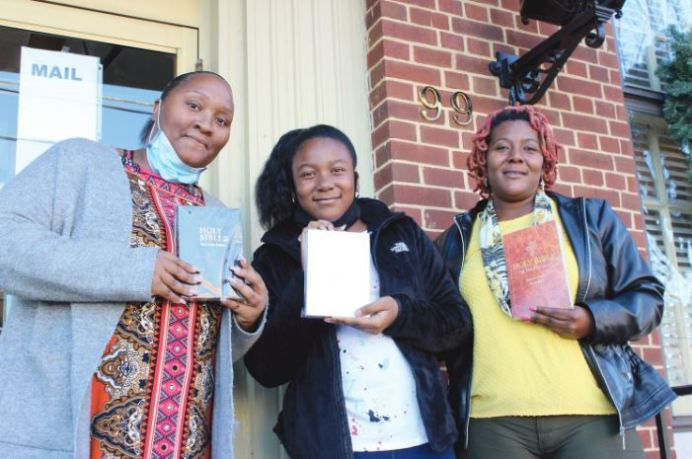 From left, Karen Robinson, 10-year-old Tyhsia Raines and Vaneshia Parker stand with a few of the Bibles they plan to hand out as Christmas gifts to strangers on Christmas Eve. Dunn Daily Record Photo