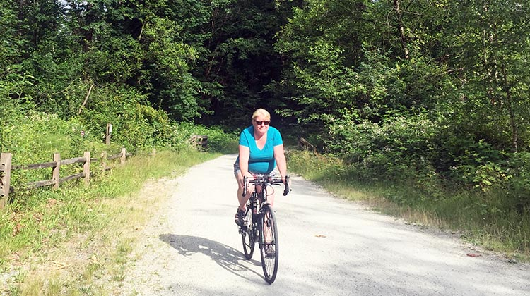 Review of the Burnaby Cariboo RV Park. Here's Maggie riding her bike along the trail next to the Brunette River