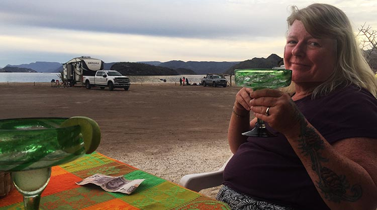 Day 5 of our RV Trip with Baja Winters: San Ignacio to Santispac Beach, Bahía de Concepción, Baja California Sur, Mexico. We made it! Maggie enjoying a well deserved margarita at Armando's Restaurant on Santispac Beach. In the background are our RV and truck