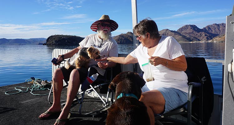 Here's Joe and Kathy on Jerry's boat. Kathy is feeding their dog Boston, while Jerry's dog Kayla gets in on the action as well! This was on the water in Bahia Concepcion, near Santispac Beach