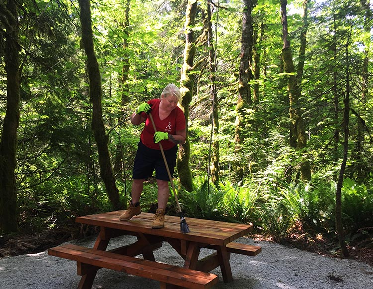 Workamping at Paradise Valley Campground, Squamish, BC, Canada. Here's Maggie cleaning picnic tables. She mainly worked in the office, but did get to join me in the fun of site clearing at least once a week!