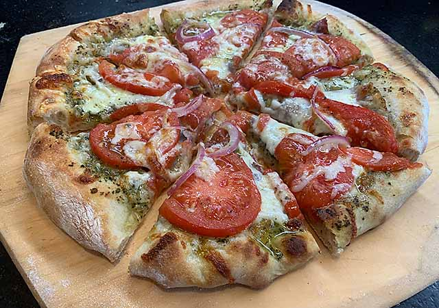 Pizza with tomatoes, pesto, Proscuitto