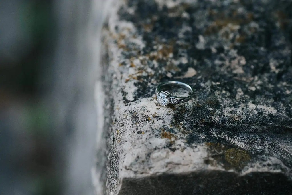 Diamond engagement ring placed on a stone slab