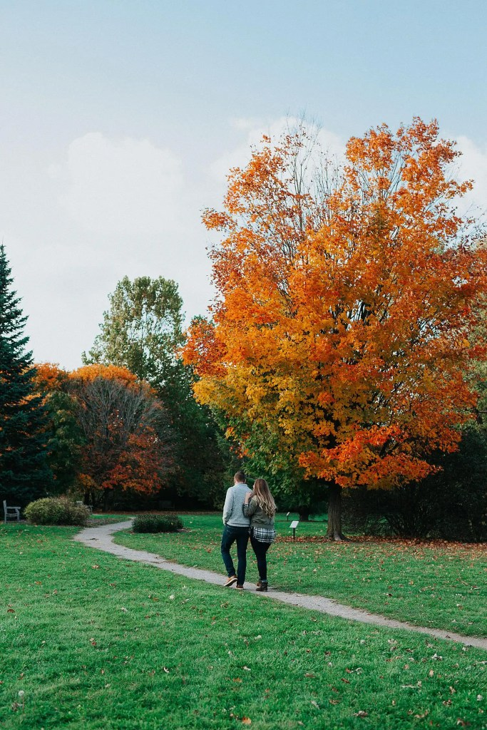 a couple walking down a path in the Guelph Arboretum surrounded by fall leaves