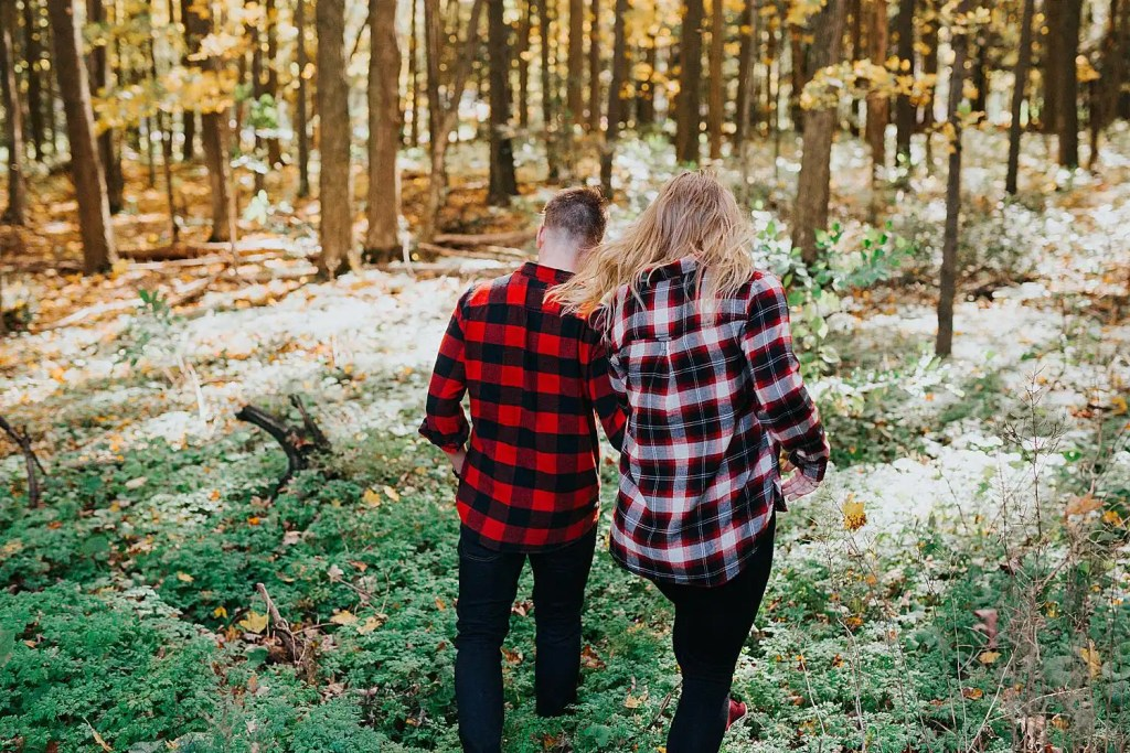 a couple running in the forest during their Toronto engagement shoot