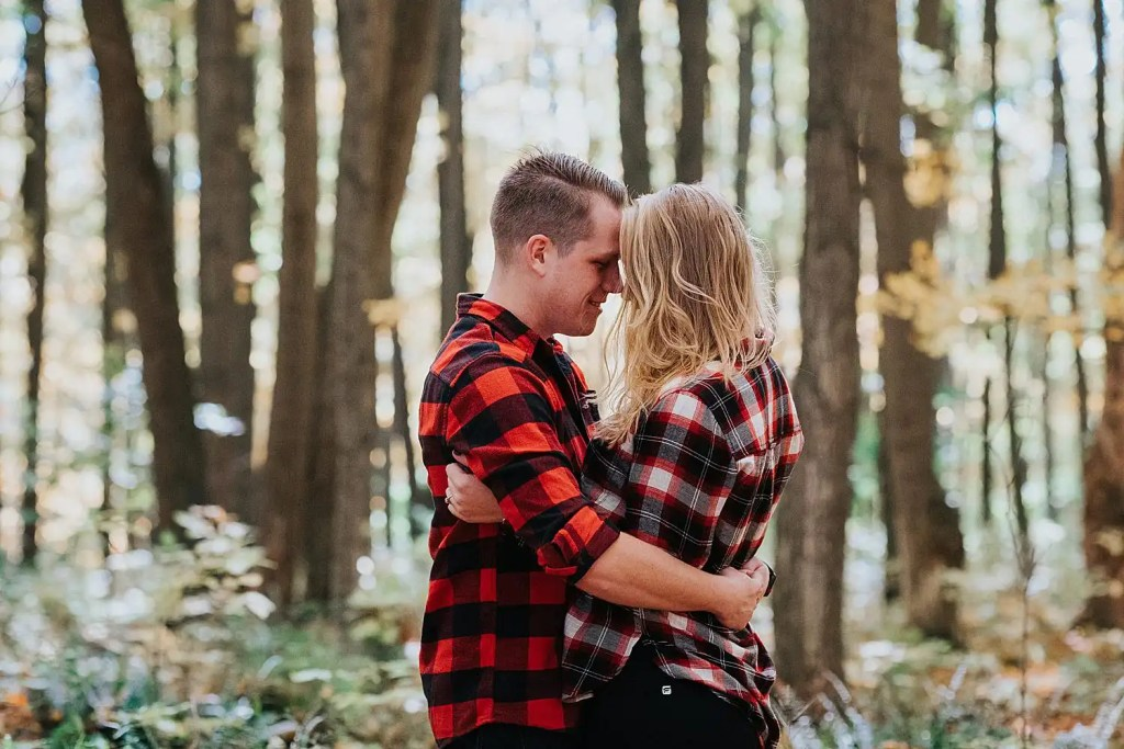 couple throwing leaves and hugging in the forest