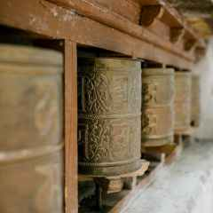 old prayer wheels with ornament in buddhist temple