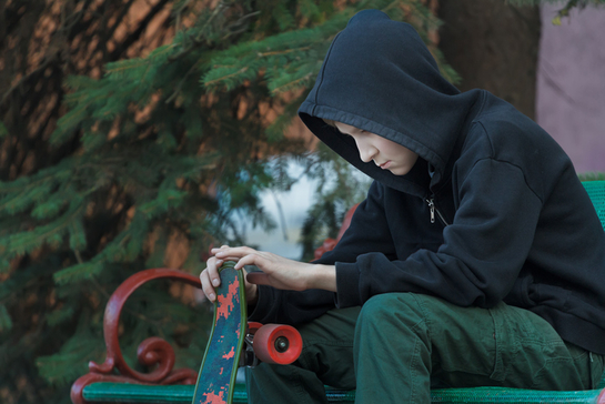 Portrait of relaxing teenager looking at skateboard in his hands