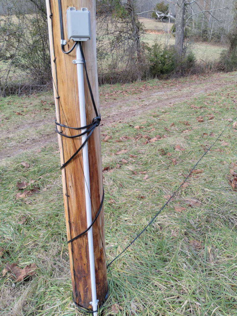 hight resolution of telephone pole with phone wire wrapped down it and extending across the ground