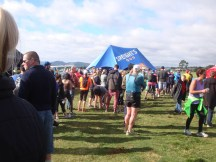 A long queue of participants waiting for a sausage sizzle and a beer.