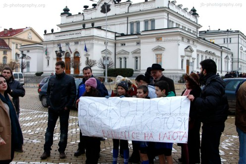 The children holding a protest sign in front of the parliament