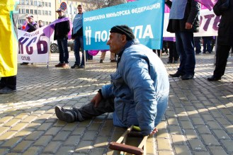 One-legged miner sitting on the street