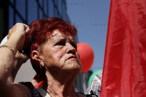 Old woman in the crowd of demonstrators, shaking her fist during a speach.