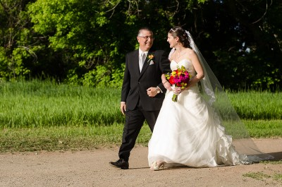 father walks bride down aisle during outdoor wedding
