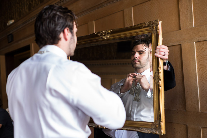 Groom putting on bowtie in mirror