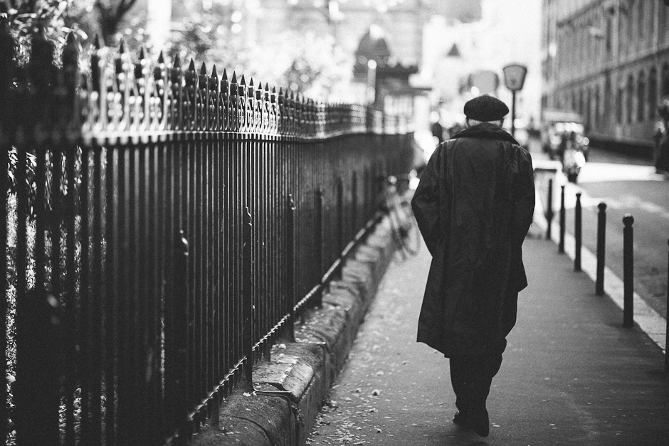 A black and white photograph of a man walking on a street in Paris, France