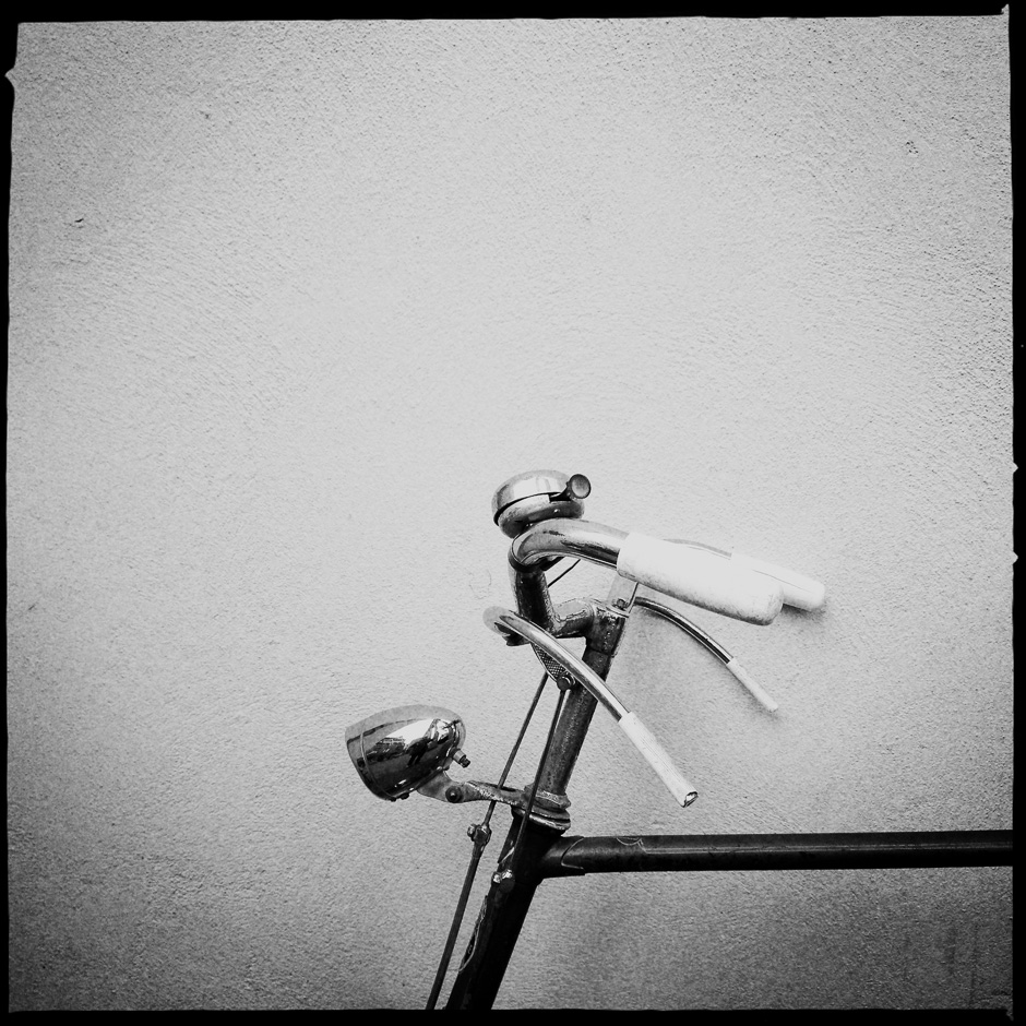 Black and white minimalistic photograph of a bicycle's handle bars in Amsterdam