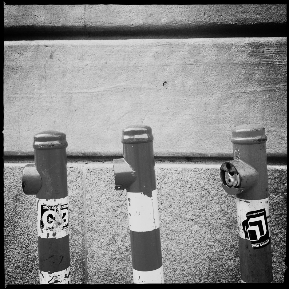 Black and White photograph of 3 metal poles against a wall taken with the iPhone and Hipstamatic