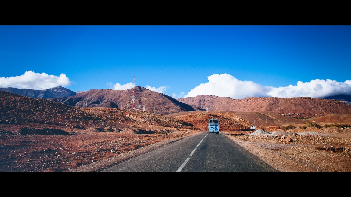 A highway in the Moroccan high atlas, with a bus in the background