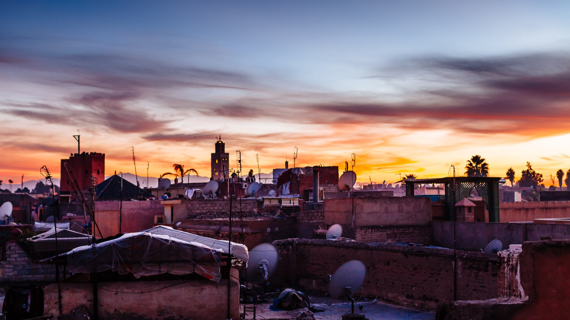 A photograph of rooftops in Marrakech at sunset shot from a balcony