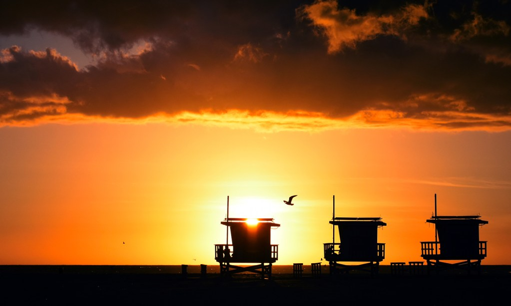 The sun sets over the Pacific behind a trio of lifeguard towers
