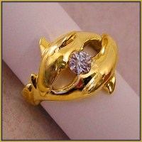 """""""Dolphins Courting"""" ring is cast in 18 karat yellow gold."""