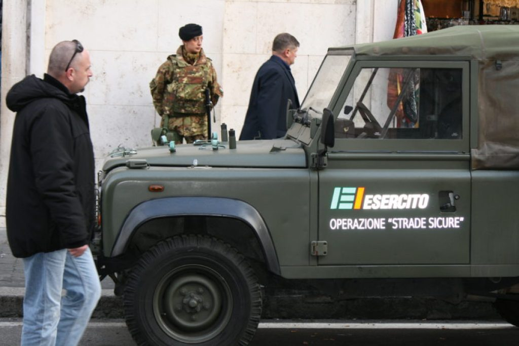 A soldier stands behind a military vehicle near the entrance to the Vatican.