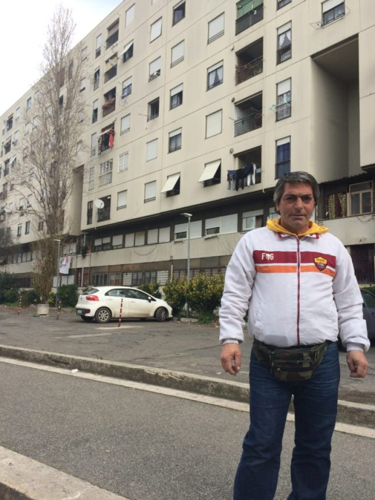 De Santis in front of his building where his brother threw himself off of and where Carlo still lives today.
