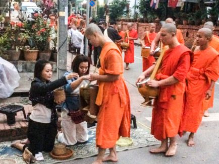Tak Bat, giving of alms, to Buddhist monks.