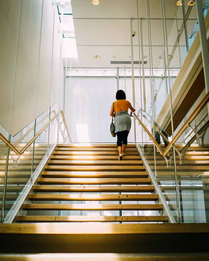woman walking on brown stair stairs staircase steps health wellness