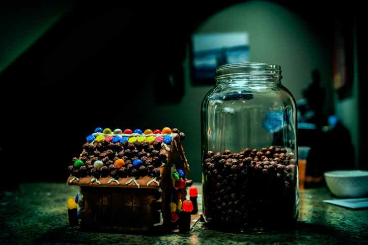 gingerbread house near clear glass jar filled with candies