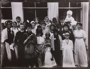 The Greene family often participated in plays and productions. In this photograph, a young Graham Greene appears on the left, dressed as a clergyman. His mother, Marion Raymond Greene, is dressed as a nurse in the back, and his father, Charles Greene, is standing to the right of her.