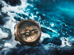 Compass on blue ocean rocks