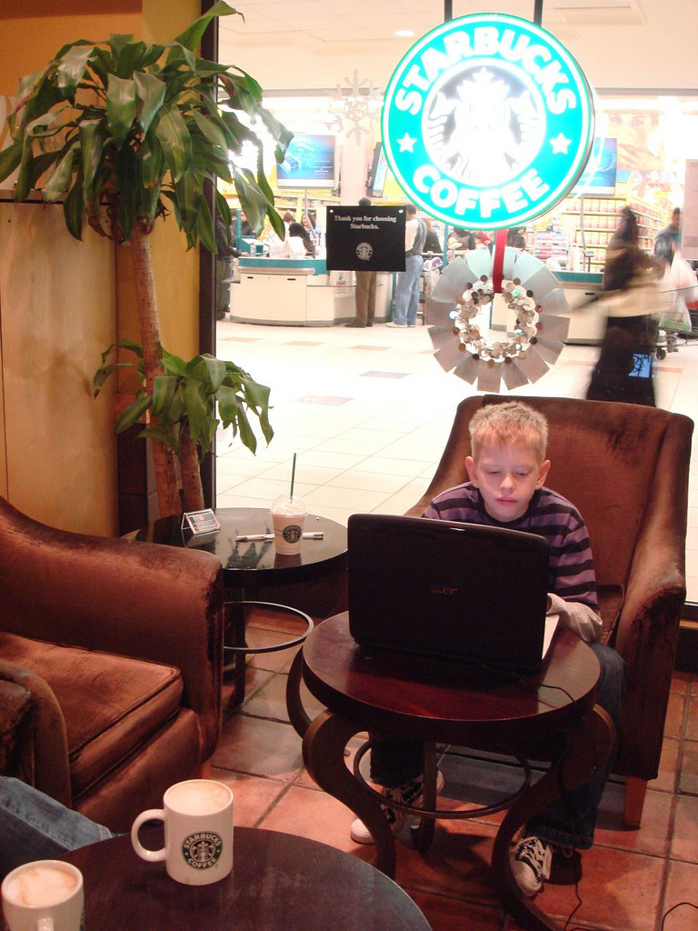 CJ as a young corporate customer on his laptop in Starbucks