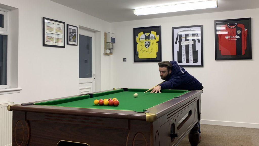 John playing pool to avoid burnout in IT