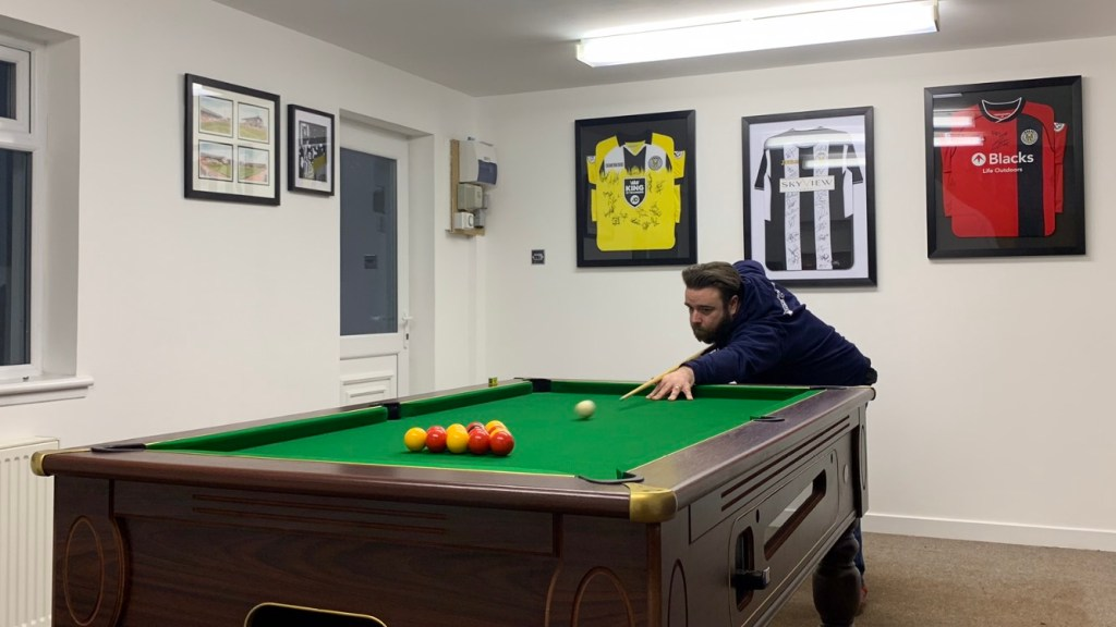 John playing pool to avoid burnout in IT