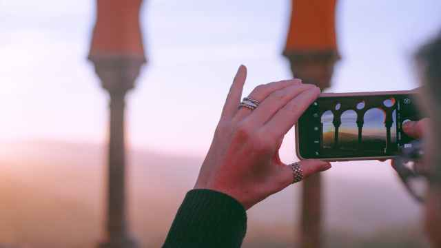 anonymous lady photographing arched palace at sundown