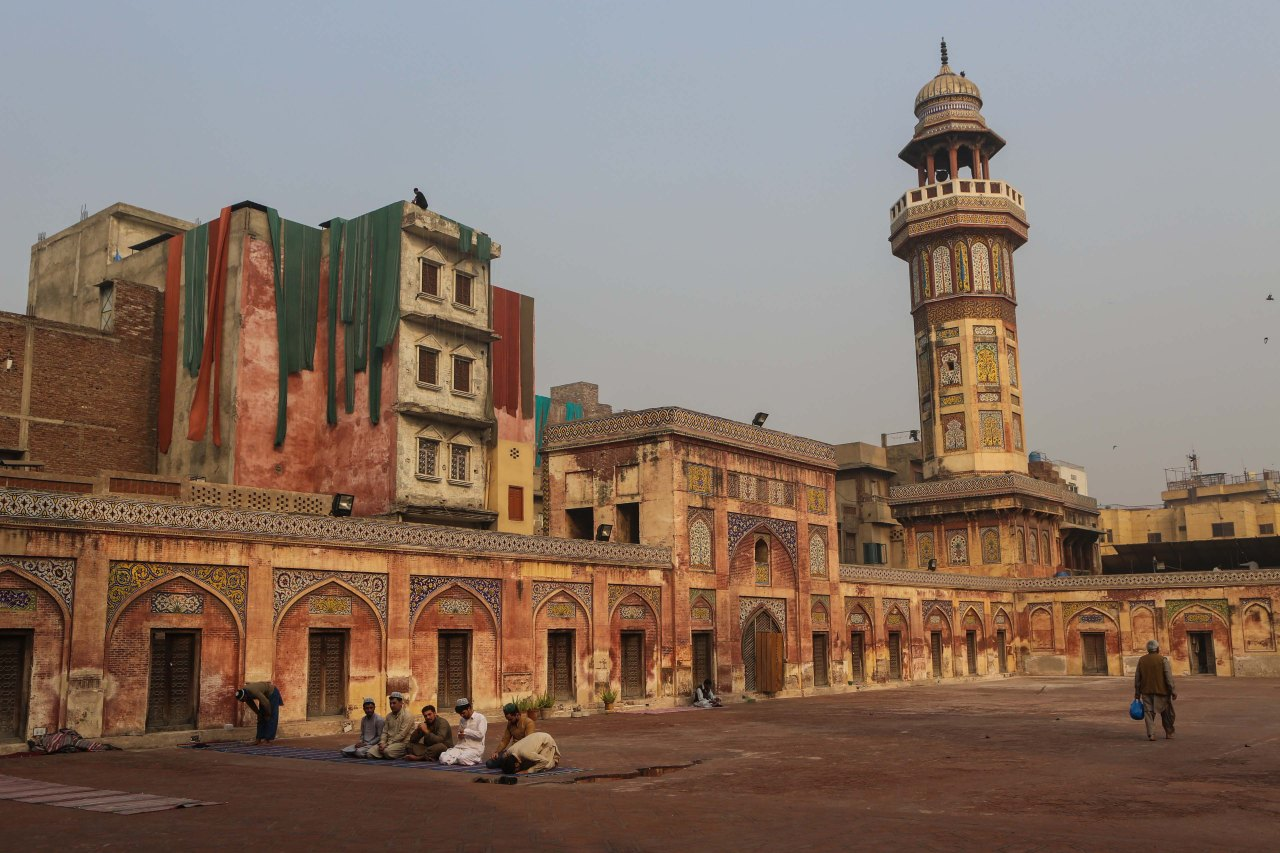 Praying in the courtyard of the Wazir Khan Mosque in Lahore. Dyed fabric drying on nearby houses