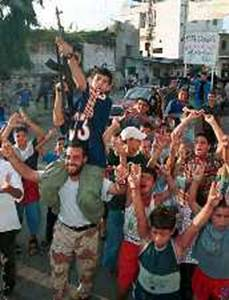 A Palestinian boy fires an assault rifle in celebration as children dance at the Ain al-Hilweh refugee camp near the port city Sidon in south Lebanon September 11, 2001.