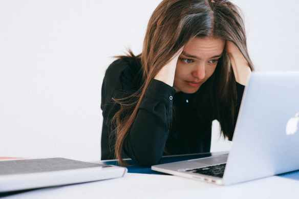 stressed woman looking at a laptop
