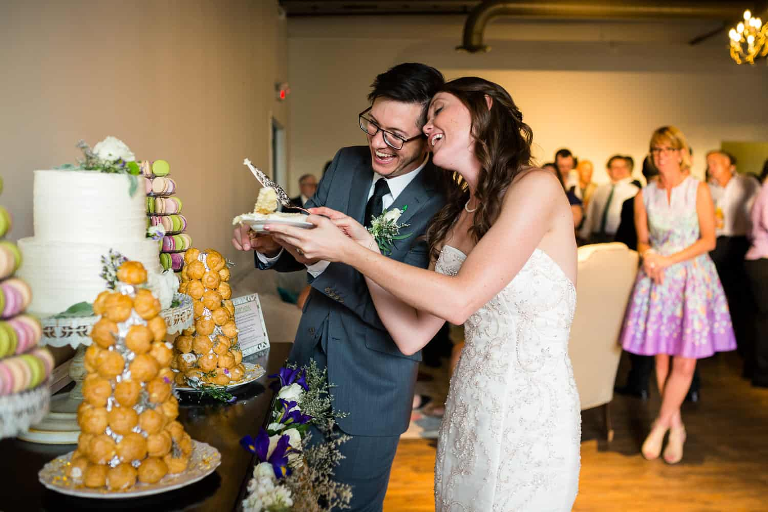 bride and groom laugh a lot while cutting their cake.
