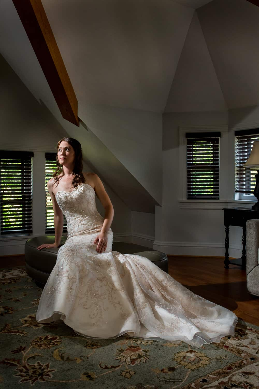 bride sitting on a stool. light shines on her dramatically from above.