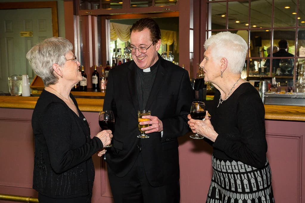 the preist shares a drink and a laugh