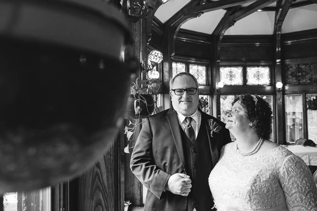 black and white photo of bride and groom near plants.