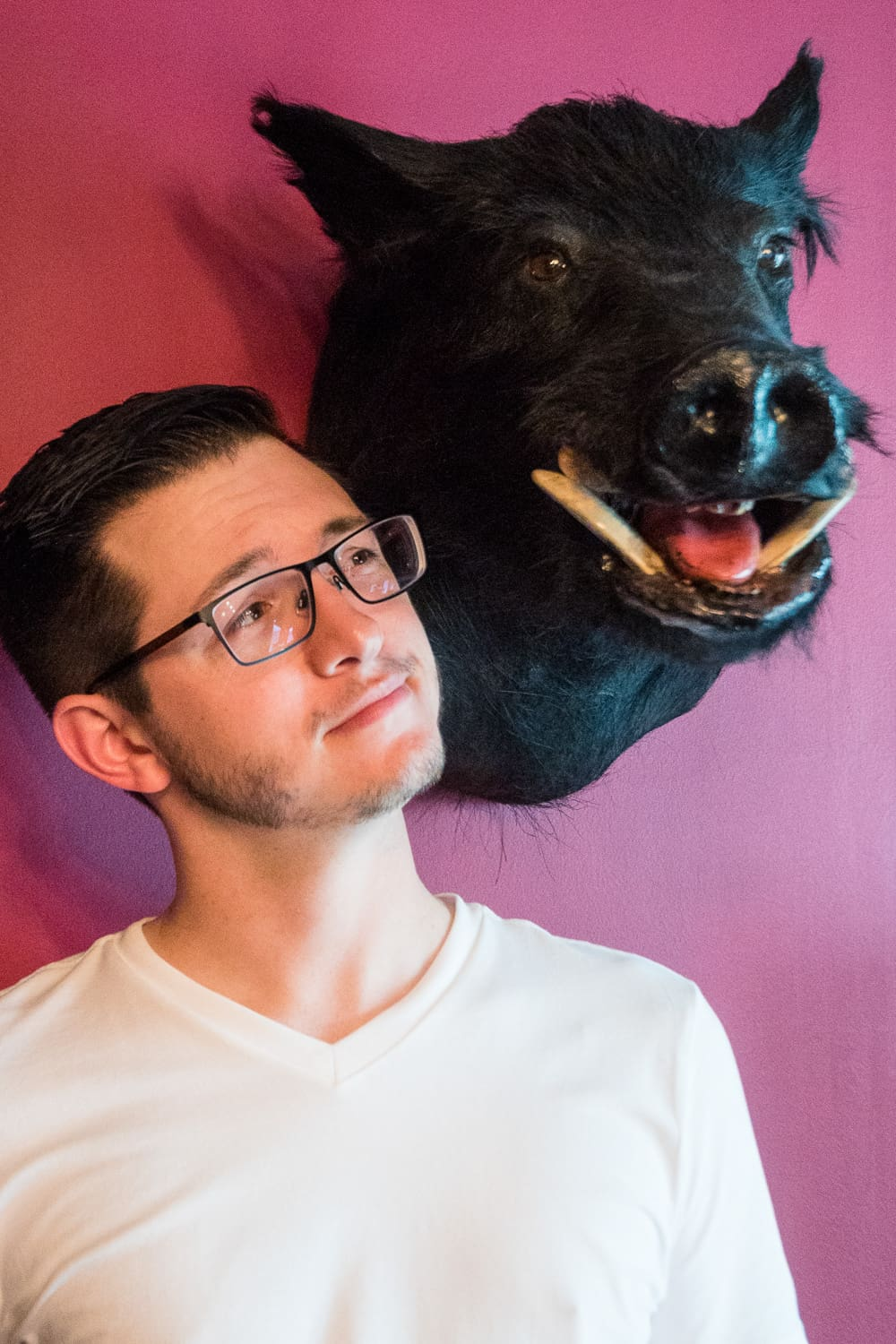 a groom standing next to a boars head mounted on the wall.